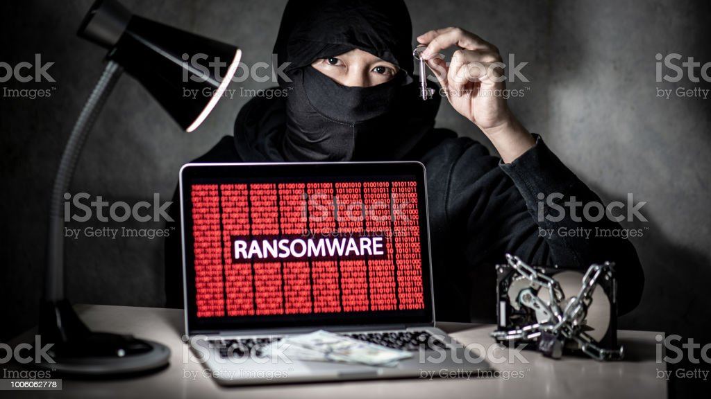 Male hacker holding key with laptop computer screen showing...