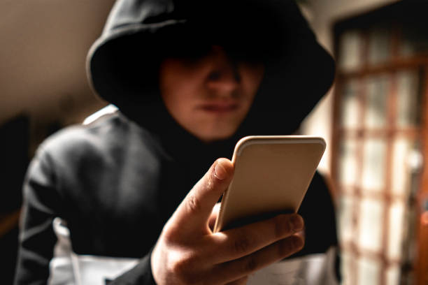 male hacker in the hood using a mobile phone, stealing your personal data f male hacker in the hood using a mobile phone, stealing your personal data terrorism stock pictures, royalty-free photos & images