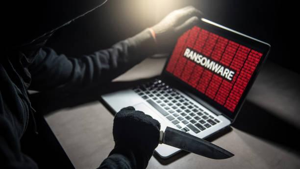 männliche hacker gewindeschneiden laptop-computer mit messer auf bildschirm mit roten digital binäre ransomware warnung angezeigt. cyber-angriff und internet security-konzept - hackmesser stock-fotos und bilder