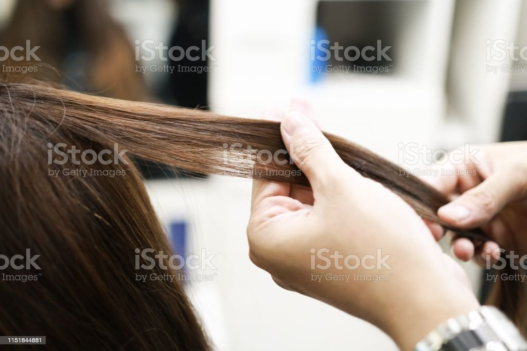 Asian woman is cutting her hair in salon