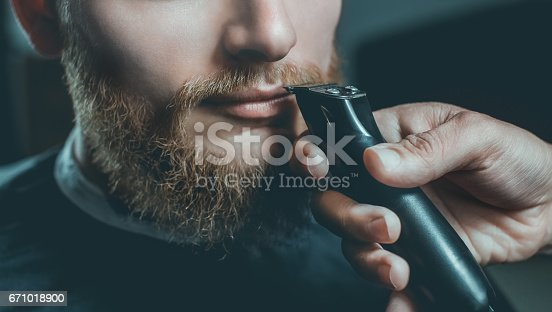 986804130istockphoto male hairdresser does a haircut of a beard and a mustache 671018900
