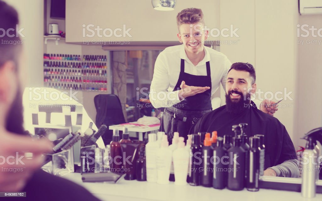 male hairdresser showing resulting haircut to client at hair salon stock photo