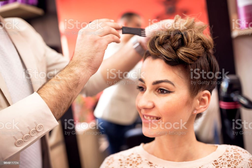Male hairdresser styling clients hair at salon royalty-free stock photo