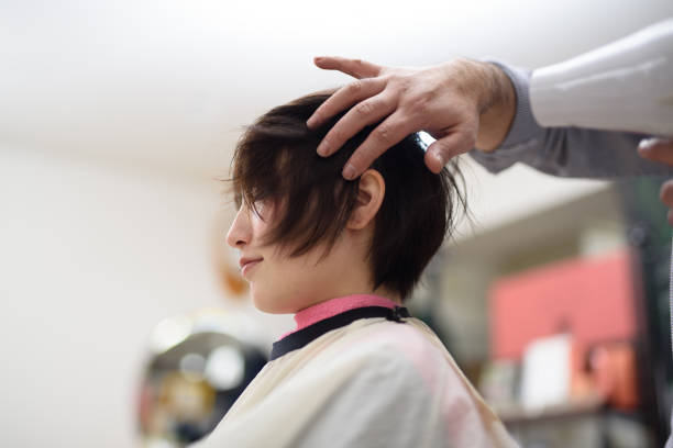ヘアサロンでお客様の髪を乾燥男性ヘアスタイリスト - 美容室 ストックフォトと画像