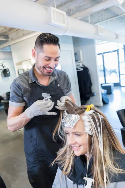 männliche friseur genießt behandlung des kunden haare farbe - folien highlights stock-fotos und bilder