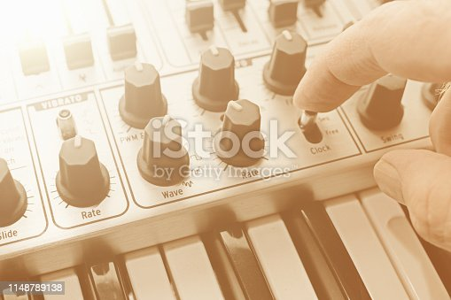 A man's hands adjust one of many controls on a retro-style analog synthesizer.