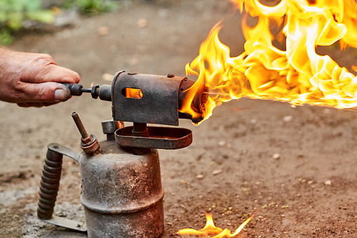 istock Male hand adjusts flame at the old rusty blowtorch. 1257550762