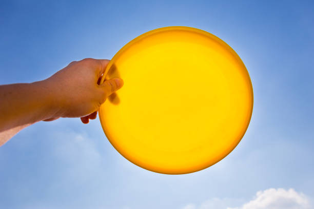 male hand catching, holding, yellow frisbee disc against blue sky background male hand catching, holding, yellow frisbee disc against blue sky background plastic disc stock pictures, royalty-free photos & images