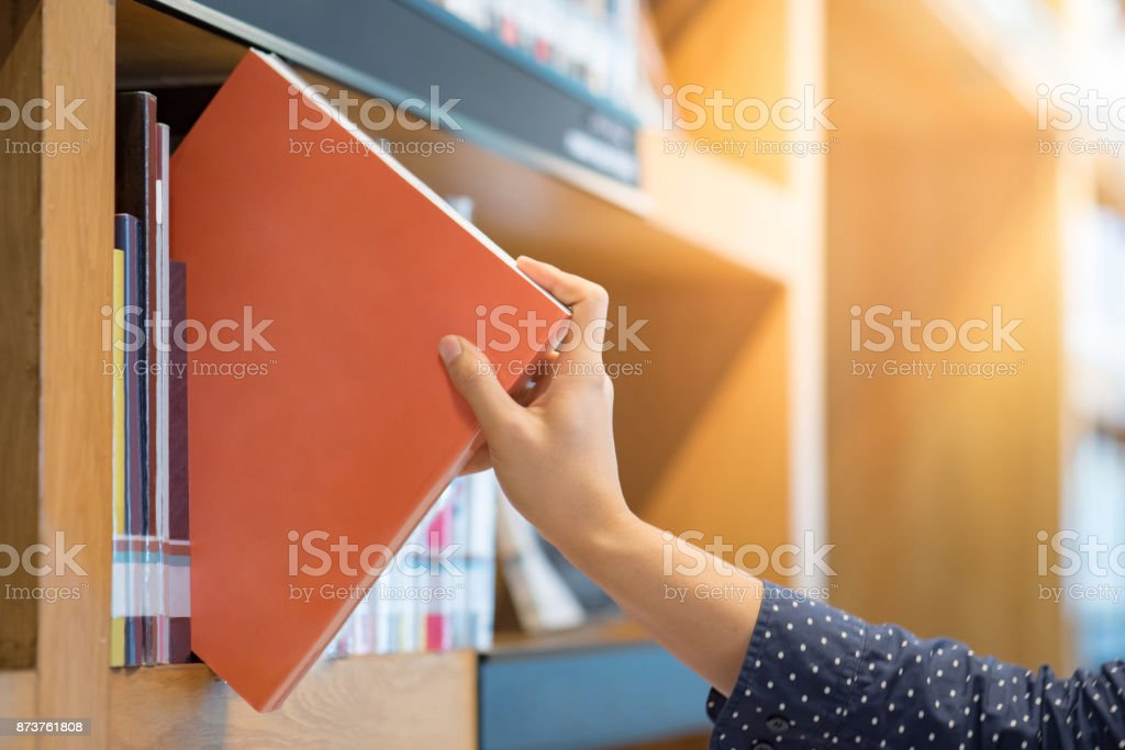 male hand choosing and picking orange book in public library stock photo