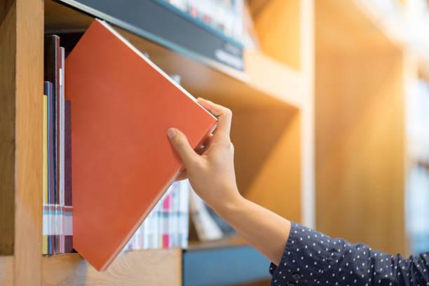 公共図書館における本の男性の手を選択してオレンジを選ぶ ストックフォト