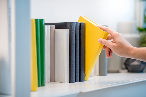 Male hand choosing and picking white book on white bookshelf in public library