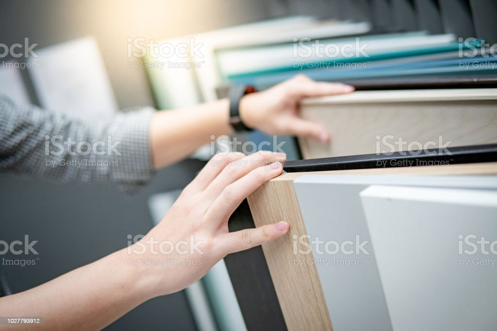 Male hand choosing cabinet panel or countertops materials for built-in furniture design. Shopping furniture and decoration. Home improvement concept stock photo