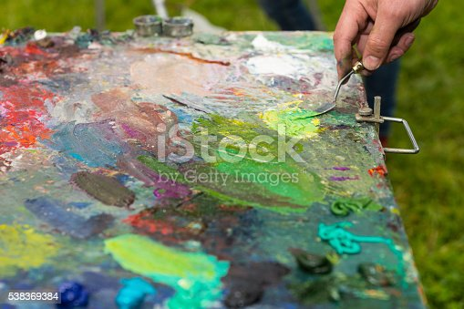504223972istockphoto Male hand cleaning off a palette with paletteknife 538369384