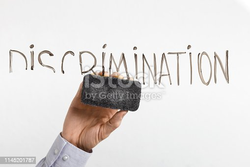 Equal rights. Male hand cleaning word Discrimination on glass board, white background
