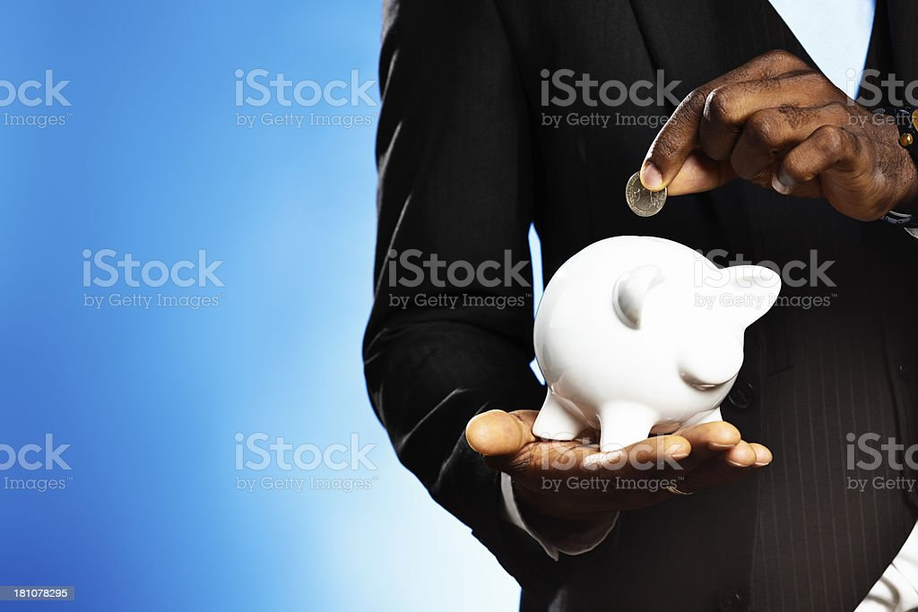 Male hand demonstrates saving by adding coin to piggybank royalty-free stock photo