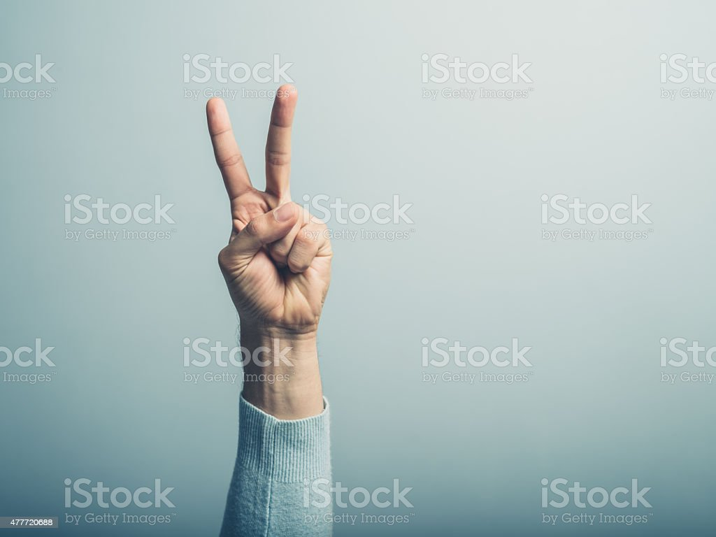 Male hand displaying victory sign A male hand is displaying the v for victory sign 2015 Stock Photo