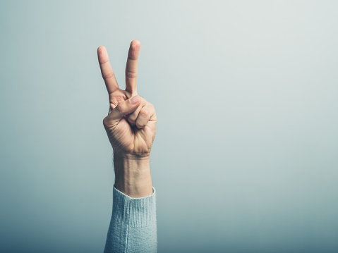 Male Hand Displaying Victory Sign Stock Photo - Download Image Now