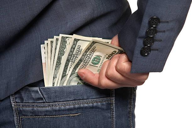 Masculino mão extrai um dinheiro no bolso da calça jeans - foto de acervo