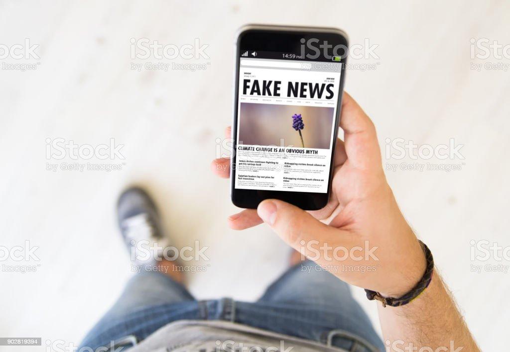 male hand fake news smart phone stock photo