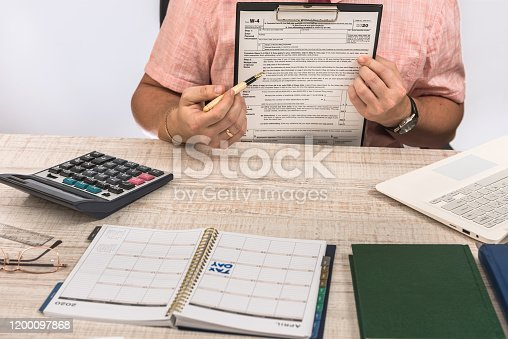 184625018 istock photo male hand filling out the W-4 form 1200097868