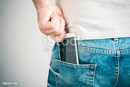 A Male Hand Grabbing A Smartphone In The Left Back Pocket Of A Jeans Trouser