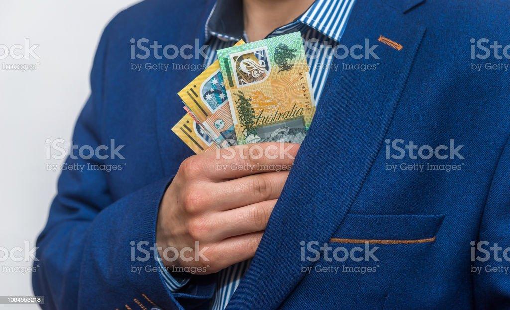 Male hand hiding australian dollar banknotes into pocket stock photo