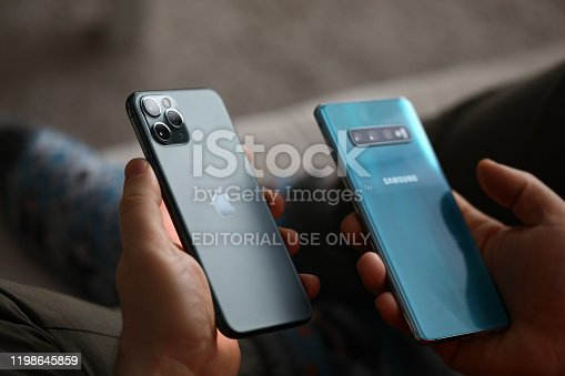Minsk, Belarus - 11 December 2019 : Male hand hold Apple iphone pro and samsung galaxy s 10.