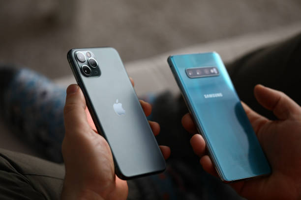 Male hand hold Apple iphone pro and samsung galaxy s 10 stock photo