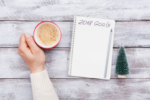 Male hand hold cup of coffee and notebook with goals for 2018. Planning and motivation for the new year concept. stock photo