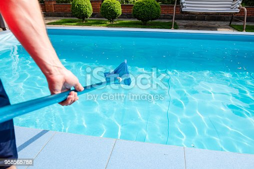Worker make maintenance of swimming pool. Male hand hold pool net cleaner.