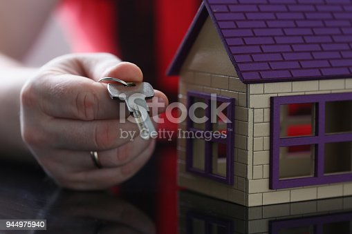 689401592 istock photo Male hand hold silver key giving 944975940