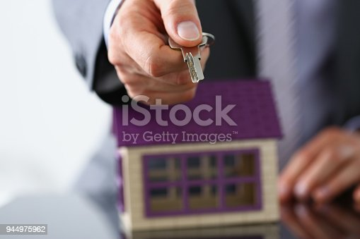 689401592 istock photo Male hand hold silver key giving 944975962
