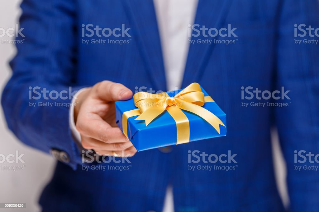 Male hand holding a blue gift box with ribbon. royalty-free stock photo
