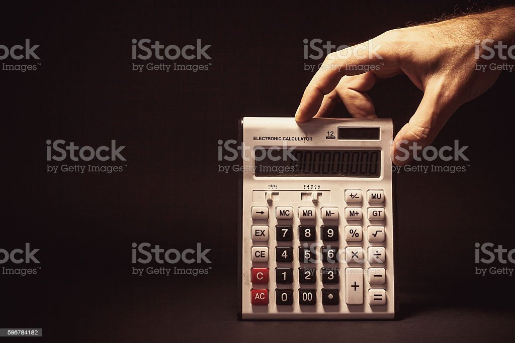 Male Hand Holding a Electronic Calculator stock photo