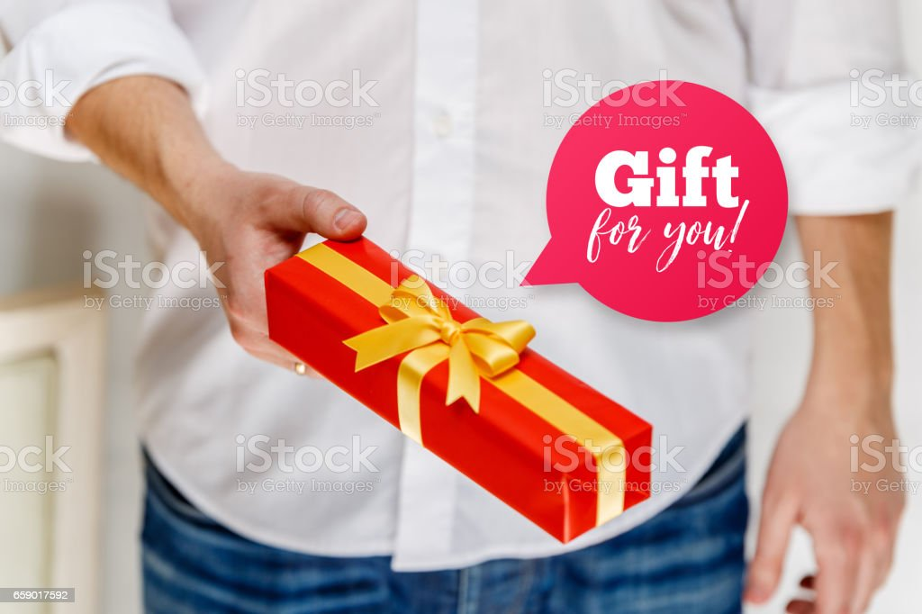 Male hand holding a red gift box with ribbon. royalty-free stock photo