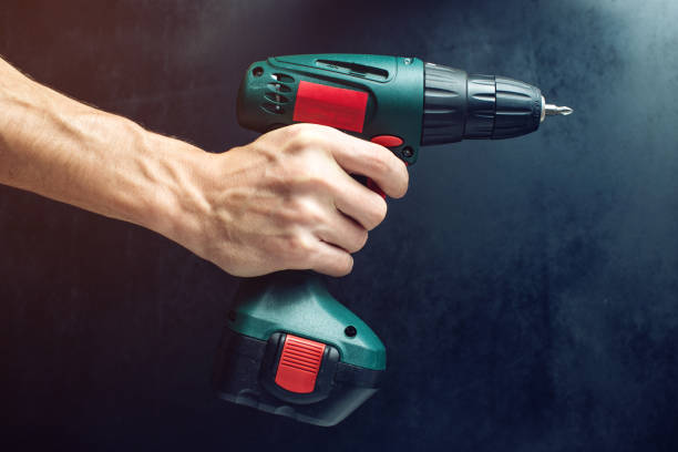 male hand holding a screwdriver, for screwing screws - drill stock photos and pictures