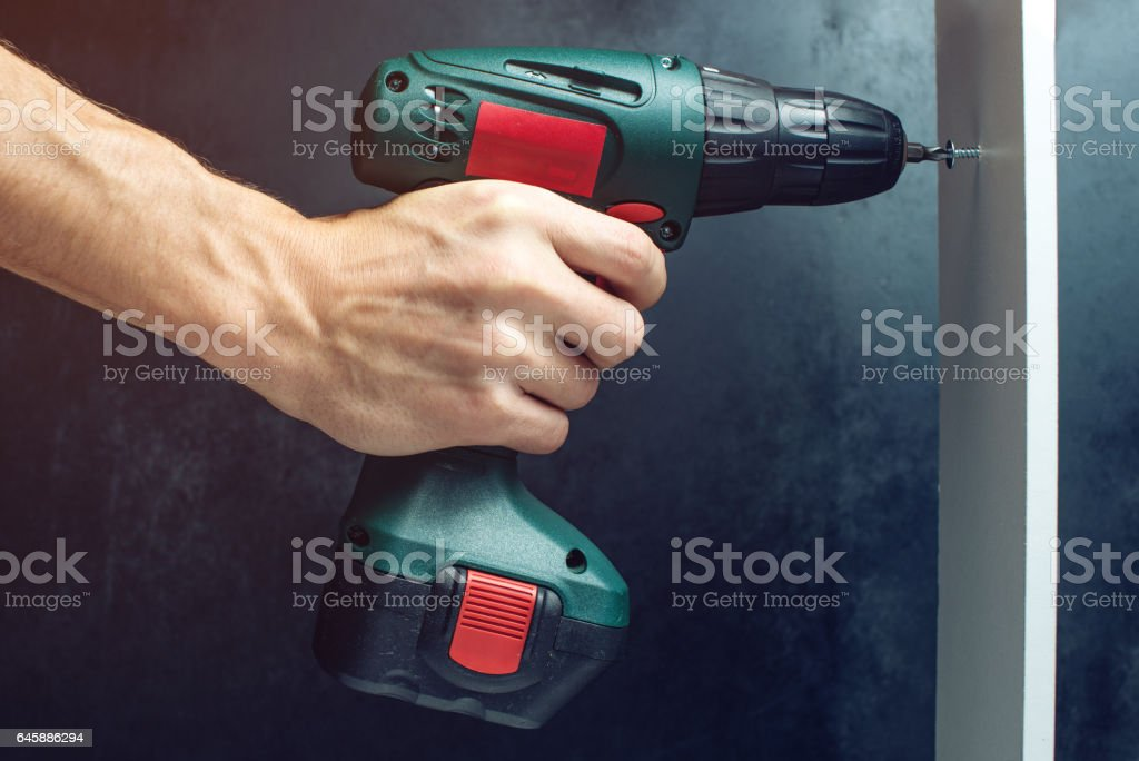 male hand holding a screwdriver, for screwing screws stock photo