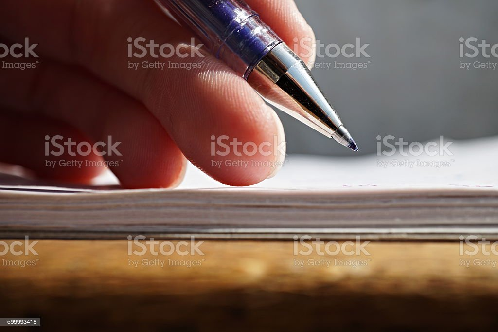 Male hand holding a sharp blue office pen stock photo