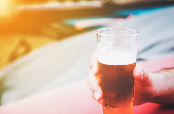 Male hand holding a small glass of cold beer stock photo