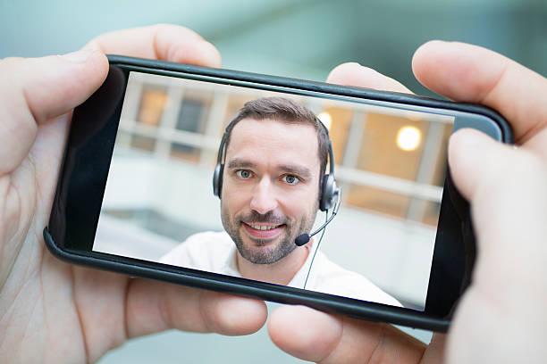 Männliche hand, die ein smartphone, während eine skype – Foto