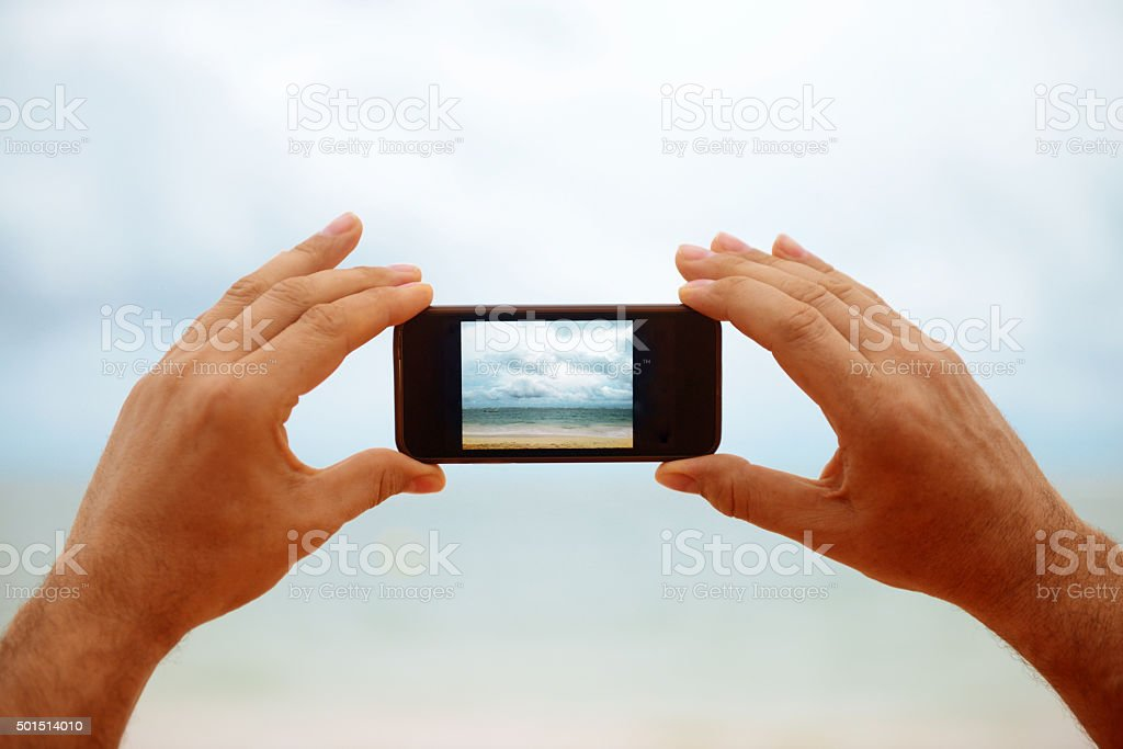 male hand holding a smartphone on a background of the sea stock photo