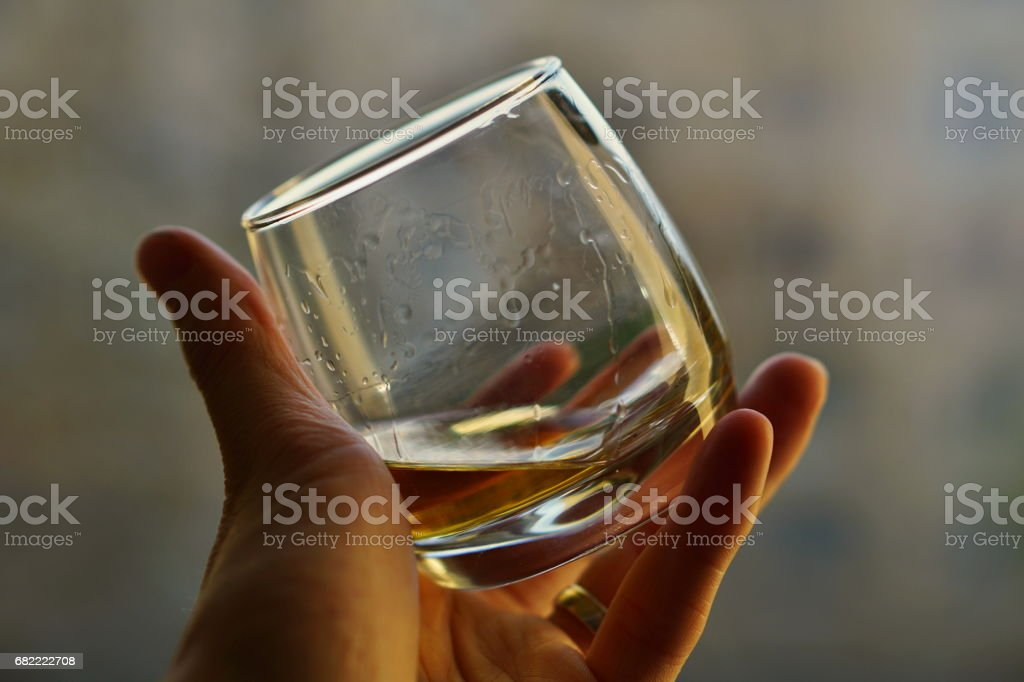 Male hand holding a whiskey glass with golden liquo stock photo