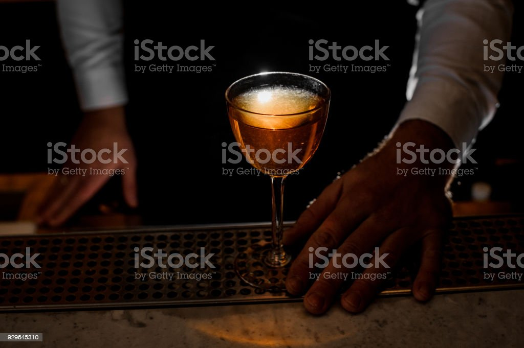 Male hand holding an elegant glass with a light alcoholic drink stock photo