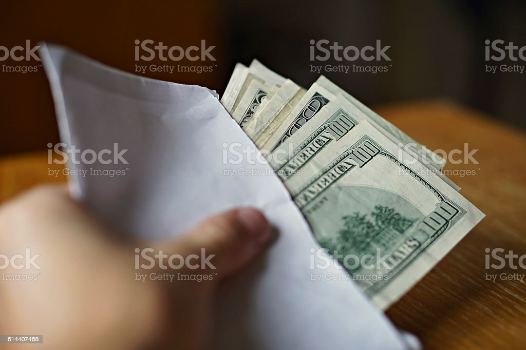 Male hand holding and passing white envelope full of Dollars stock photo