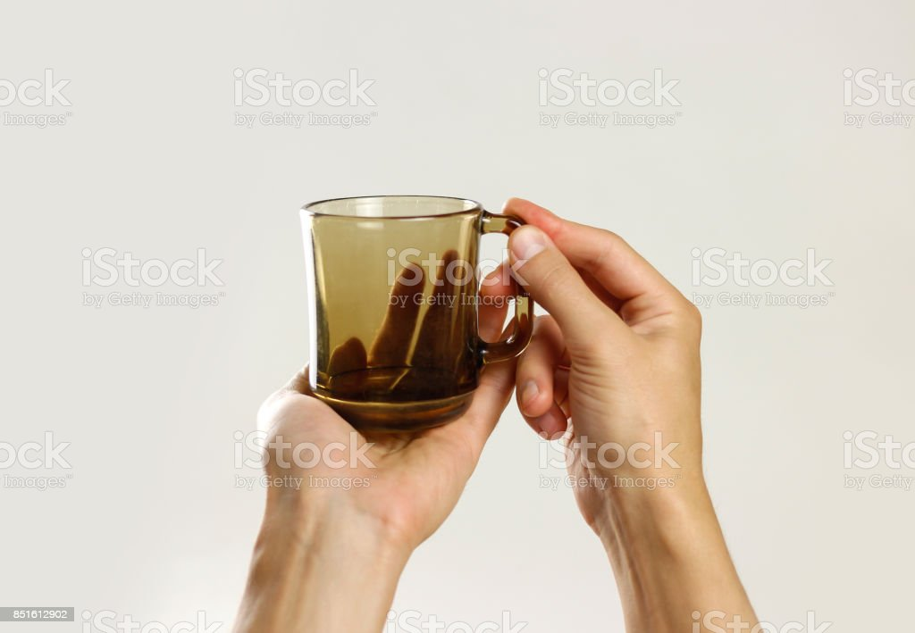 Male hand holding black empty glass mug. Isolated on gray background. Closeup stock photo