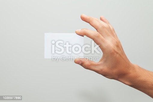 istock Male hand holding blank business card 1035977890