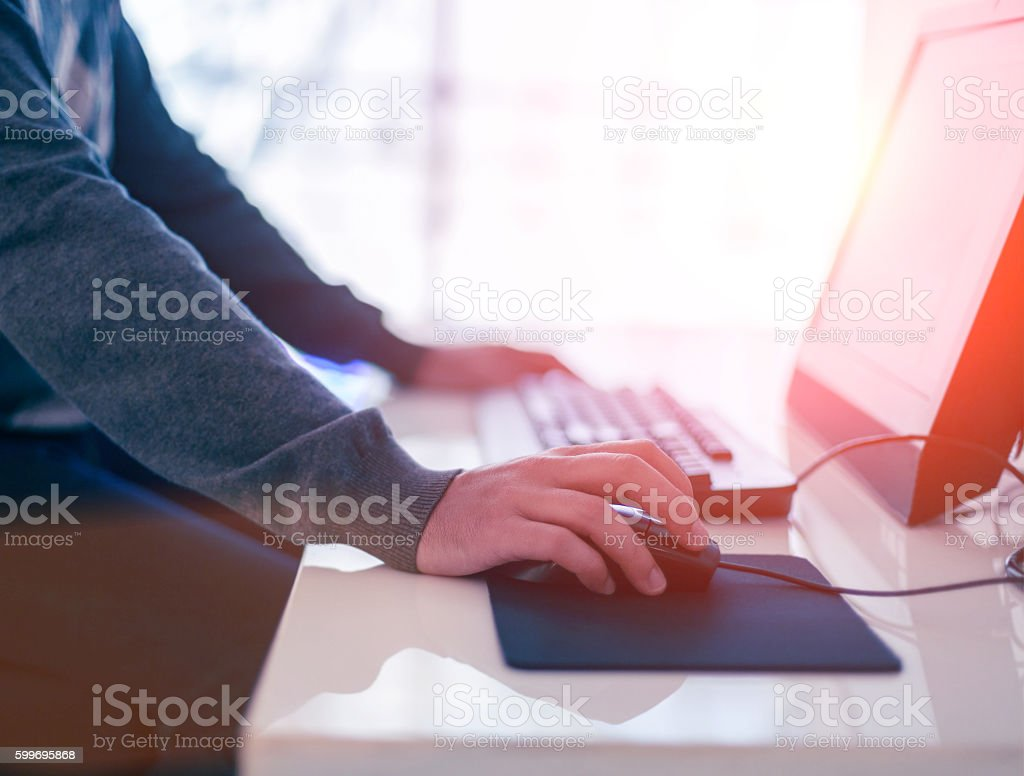 Male hand holding computer mouse with laptop keyboard stock photo