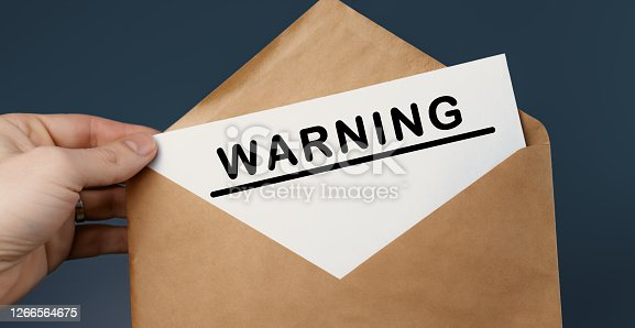 istock Male hand holding craft envelope with text WARNING on blue background 1266564675