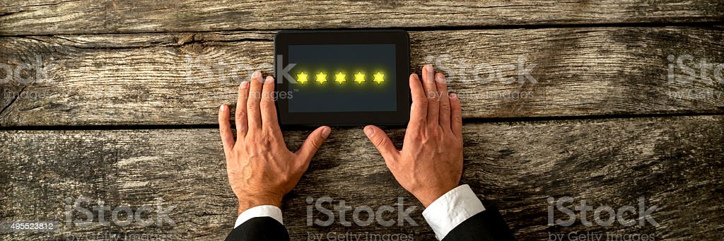 Male hand holding digital tablet with five golden stars stock photo