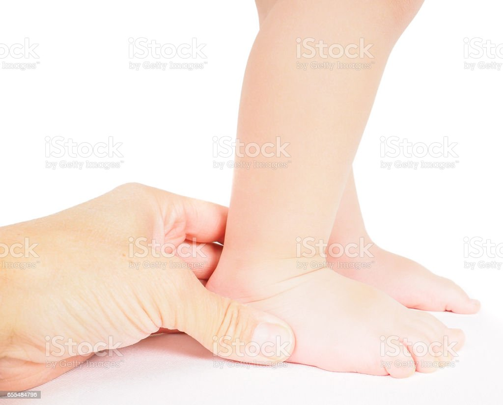 Male hand holding firmly around a foot of toddler isolated on white - foto stock